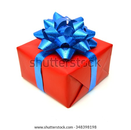 Red christmas gift box tied with blue ribbon bow on white background