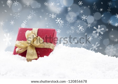 Red Christmas gift with gold ribbon on black and white defocused lights background - stock photo