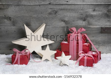 Red Christmas gifts with wooden starts on grey wooden background. - stock photo