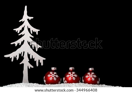 Red christmas glitter-balls and a white christmas tree - isolated over black - stock photo