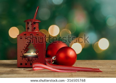 Red Christmas lantern and balls on a wooden table. Christmas tree and lights at the background. - stock photo