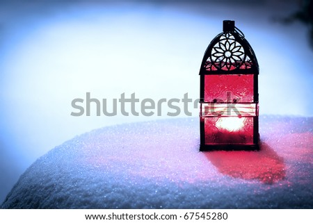 Red Christmas lantern in snow, with yellow candle light - stock photo