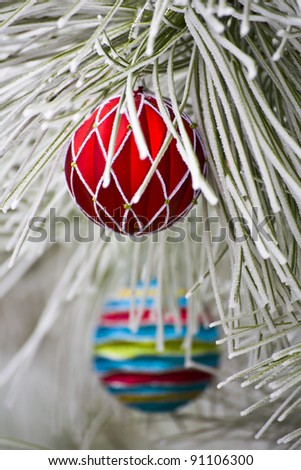 Red Christmas Ornament hanging on a frost covered pine tree outdoors - stock photo