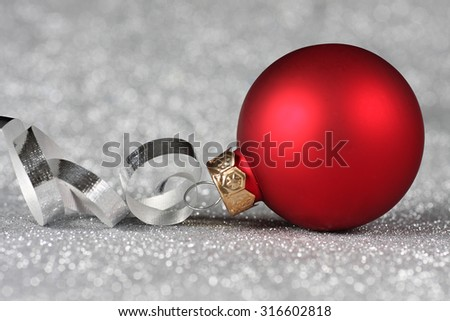 Red Christmas ornament with curled ribbon on a silver background