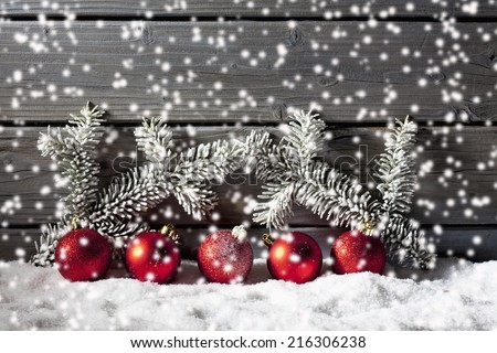 Red christmas ornaments on pile of snow against wooden wall - stock photo