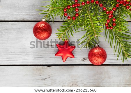 Red christmas ornaments with green boughs and pearl on a wooden table. - stock photo