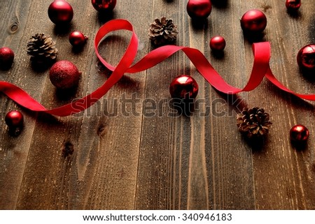 Red Christmas ornaments with ribbon on black wooden background