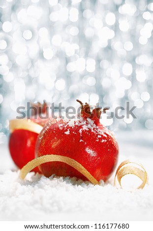 Red Christmas pomegranates in a bed of wintery snow with a gold ribbon and a bokeh of festive twinkling lights with copyspace for your seasonal greeting - stock photo