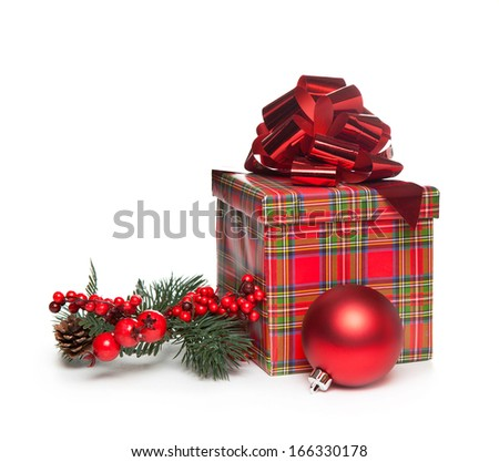 red christmas present with bow, mistletoe and red ball over white background