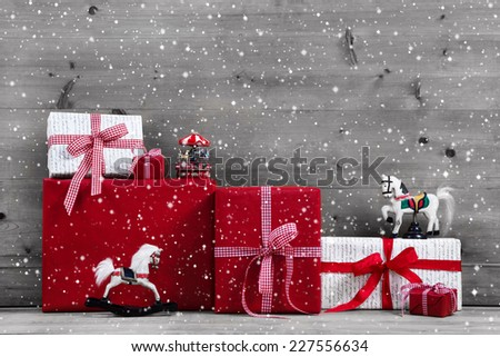 Red Christmas presents and gift boxes with rocking horse on grey wooden background. - stock photo