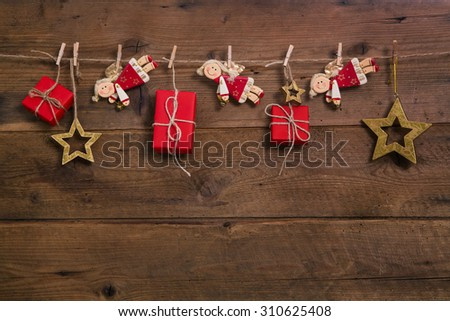 Red christmas presents with golden angels hanging on an old wooden wall. - stock photo