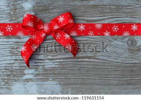 Red christmas ribbon bow on wooden board with copy space - stock photo