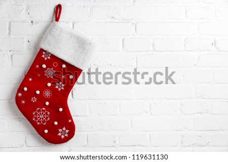 Red Christmas sock hanging on white brick wall - stock photo