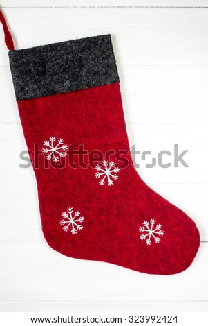 Red Christmas sock with snowflakes for Santa gifts hanging on wooden background.  - stock photo