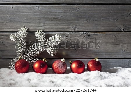 Red christmas spheres on pile of snow against wooden wall - stock photo