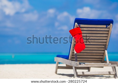 Red Christmas stocking on chair longue at tropical white beach - stock photo