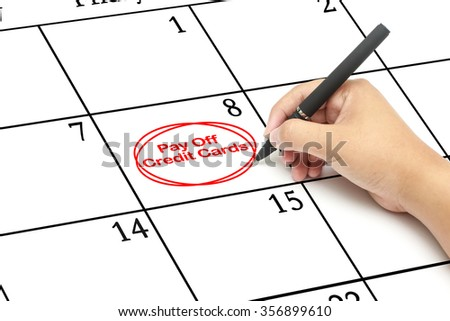 Red circle.Mark on the calendar with  words Pay off credit cards written on a calendar to remind you an important appointment