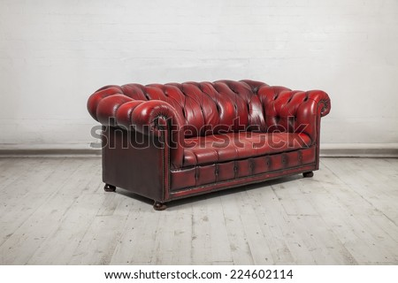 red classic chesterfield sofa in warehouse - stock photo