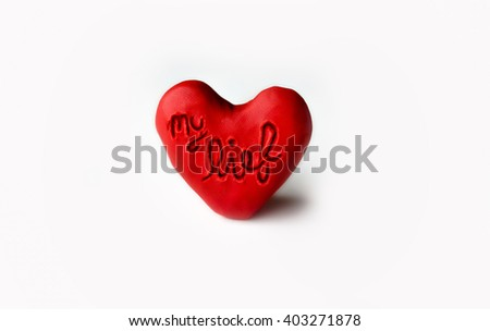 "Red clay heart with ""my love"" engraved on white background"