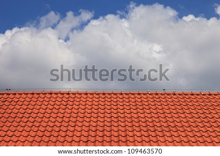 Red clay tiles roof pattern on blue sky background. - stock photo