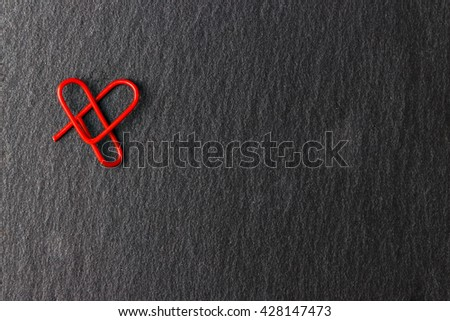 Red clip heart-shaped on black background. Love concept for lovers.