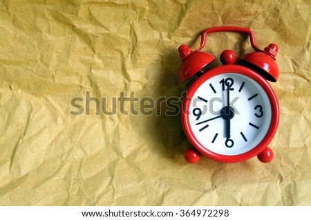 Red clock on wrinkled brown paper background - stock photo