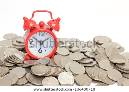 Red clock staying on coins. Time is money concept - stock photo