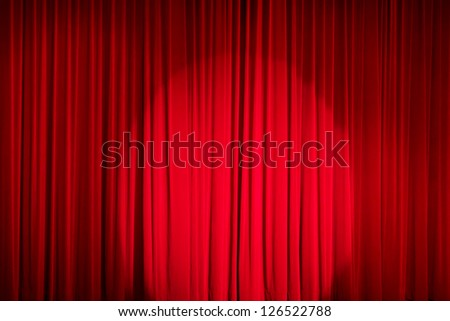 Red closed curtain with a light spot in a theater - stock photo