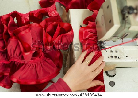 Red cloth and ribbon sewn and ruffled through a sewing machine - stock photo