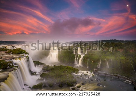 Red clouds and full moon during the sunrise at Iguassu Falls - stock photo