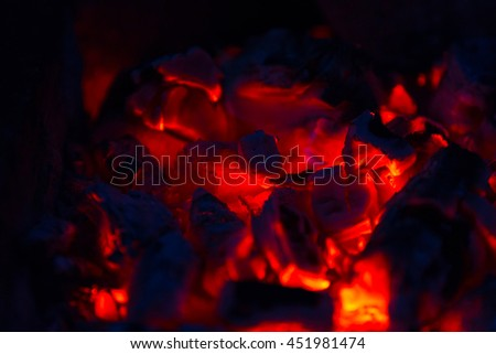 Red coals of the campfire in the dark night closeup