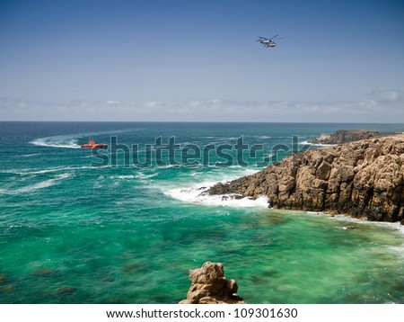 Red coastguard boat and white rescue helicopter above green ocean water and rocky shore - stock photo