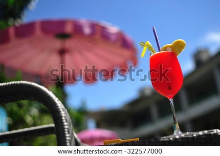 Red cocktail at pool - stock photo