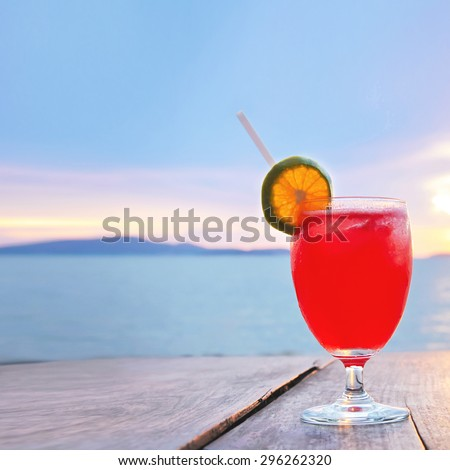 Red cocktail drink on wood table in twilight sea & sky background - stock photo