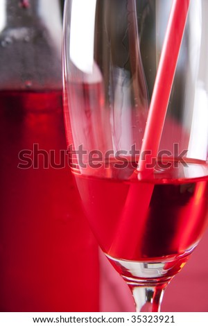 Red cocktail in a glass with a straw and a bottle in the background