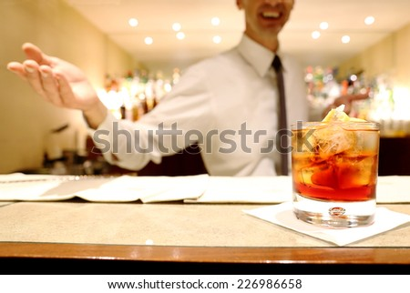 red cocktail over counter bar with smiling barman in the background - stock photo
