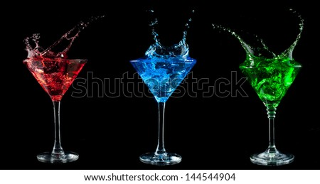 red cocktail splashing into glass on black background - stock photo