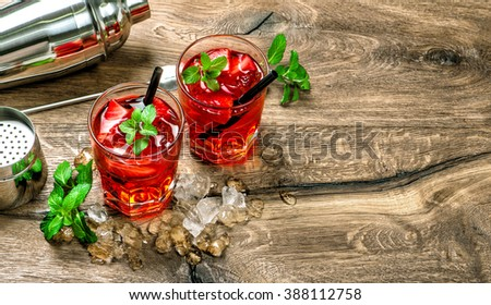 Red cocktail with ice, mint leaves and strawberry on wooden background - stock photo