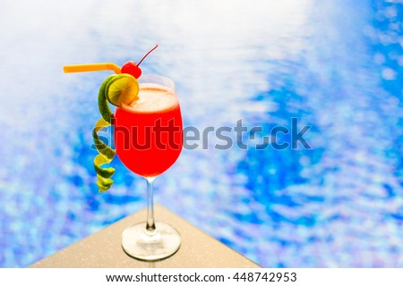 Red cocktail with lime at pool, right of frame.