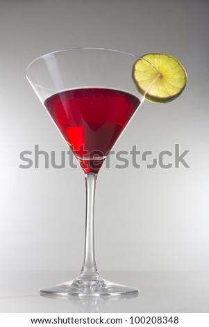 Red cocktail with lime slice - stock photo