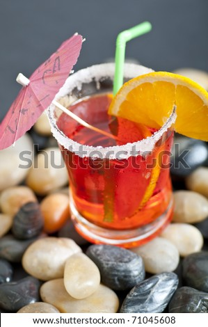 red cocktail with orange and stones - stock photo