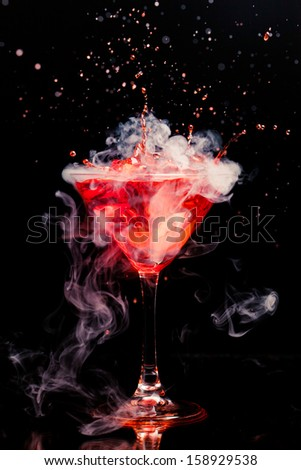 red cocktail with splash and ice vapor - stock photo
