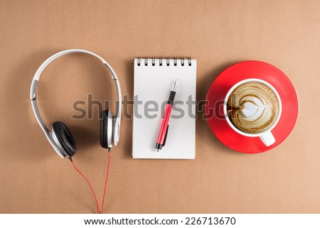 Red coffee cup, headphone, notebook, pen on wooden table. View from above. Isolated on white background  - stock photo