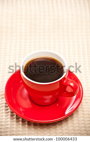 red coffee cup on tablecloth