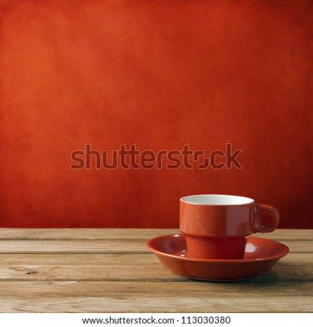 Red coffee cup on wooden deck tabletop against red grunge wall - stock photo