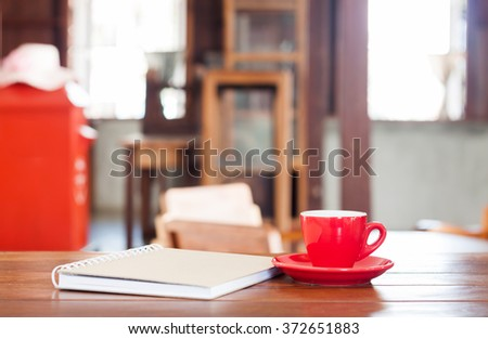 Red coffee cup with notebook on wooden table in coffee shop