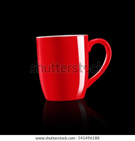 Red coffee mug with shadow on dark background.