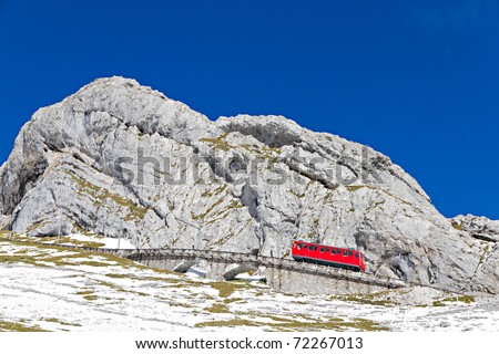 red cogwheel train serving tourists going up mountain Pilatus, Switzerland - stock photo