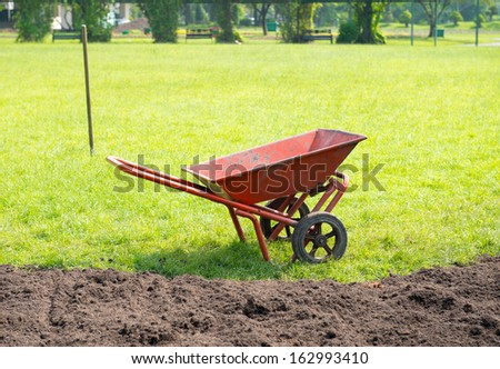 red color construction wheelbarrow in site