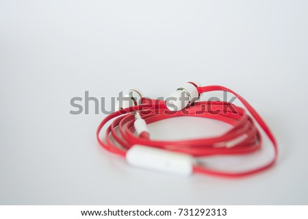 Red color earphone on white background.